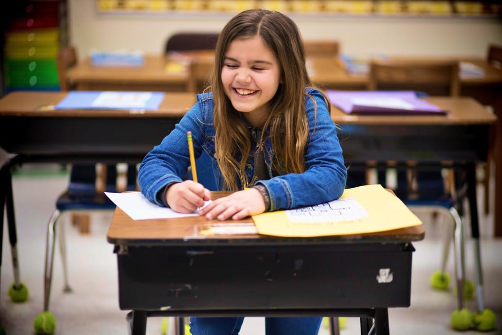3rd grader at school sitting in desk writing laughing